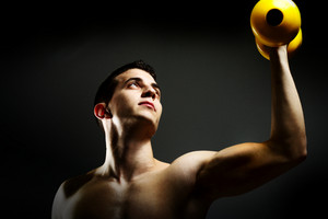Modybuilder doing heavy weight exercise with dumbbells against dark background