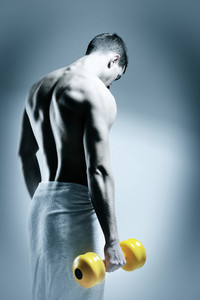 Rear view of a young male bodybuilder doing heavy weight exercise with dumbbells against dark background