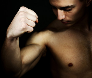 Young male showing biceps and fist
