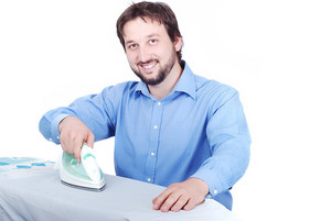 Happy young man ironing clothes