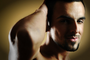 Handsome muscular man posing against dark background