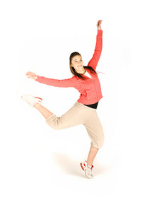 Studio isolated. Dancing female teenager  in pink with brown long hair and happy smiling facial expression jumping up.