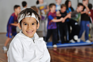 Beautiful kid in front of friends in gym hall