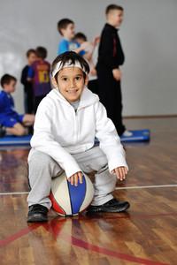 Young boy sitting on basketball