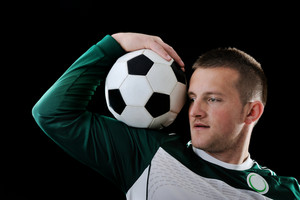 Proffessional footballer holding a ball on his shoulder