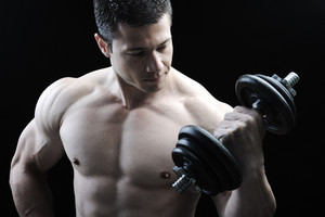 The Perfect male body - Awesome bodybuilder posing with dumbbells