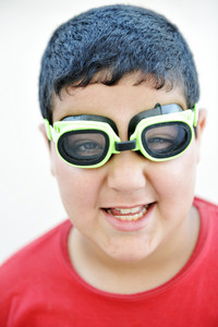 Happy funny cute  boy with the pool swimming goggles