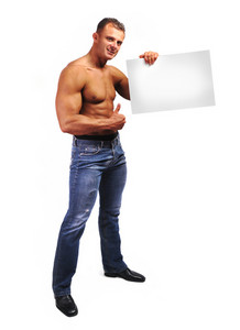 Young attractive male body builder with advertising copy space board. Studio shot
