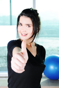 Fitness sporty girl  excercising with a ball and showing a thumb up with smile