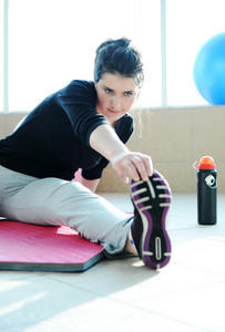Fitness sporty girl with a ball at gym and bottle of water excercising