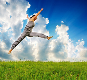 Young sporty woman runing and jumping on meadow