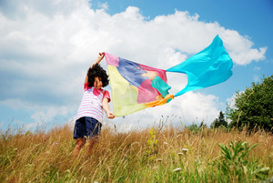 A little cute girl holding scarf on wind