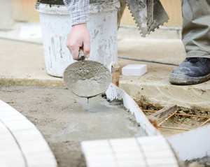 Mason worker making sidewalk pavement with stone blocks