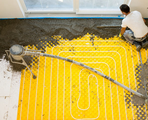 Manual worker installing underfloor heating and colling pipes