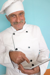 Senior cook with mustache using tablet for recipe