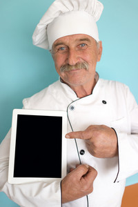 Elderly chef in white cook uniform pointing on tablet display