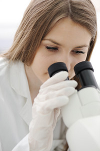 Female medical doctor using microscope in a laboratory