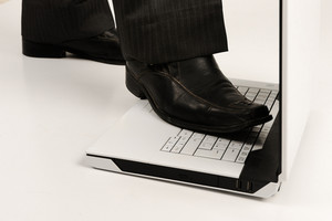 Business foot walk over laptop with white background