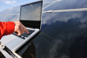 Pressing enter button on laptop at  photovoltaic solar panels