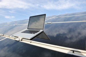 Laptop on  photovoltaic solar panels against blue sky