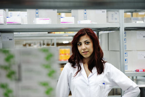 Young cheerful female worker in modern drug warehouse