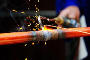 Welder using torch on metal object