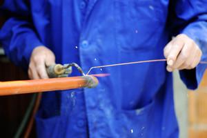 Worker in blue suit welding metal