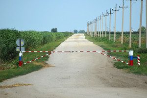 Road closed barrier. dirt road among the agricultural fields. closed zone.