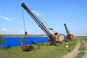 Old dragline near the blue fence. old equipment for digging the soil in canals and quarries.