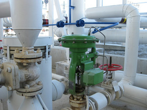 Green pneumatic valve on the pipeline. the equipment of the oil plant.