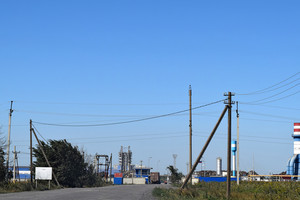 Access road to the big plant for processing scrap metal. huge factory old metal refiner. blue roof of the factory building. exhaust pipes