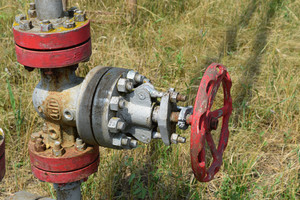 Oil valve with rocking in the background. the gate on an oil well