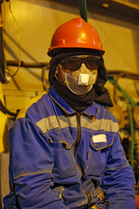 The worker in overalls and a respirator. protective attire of technical workers.