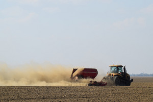 Tractor rides on the field and makes the fertilizer into the soil. clouds of dust from the dry soil tractor trailer. fertilizers after plowing the field.