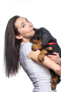 Brunette girl biting her doberman puppy by ear