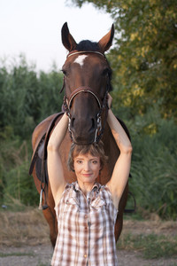Woman hold horses head up