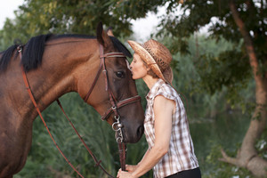 Woman in hat kissing the horse.