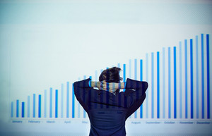 Rear View Of Businessman With His Hands Behind Head Looking At Chart On The Wall