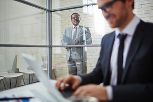 African Businessman In Suit Looking At Colleague Working In Office