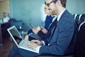 Young Businessman Typing At Seminar On Background Of Other Employees