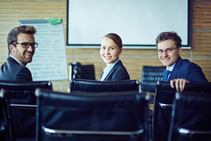 Happy Co-workers Looking At Camera In Conference Hall