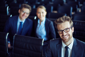 Elegant Businessman In Eyeglasses Looking At Camera With Two Employees Behind