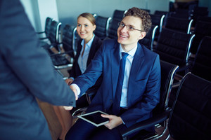 Male Employee In Suit And Eyeglasses Greeting His Partner At Conference