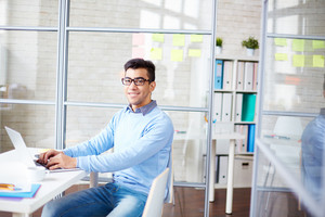 Cheerful Businessman In Casualwear Sitting By Desk In Office