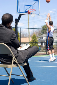 A basketball coach in a business suit observing a player on the team.   He could be also be recruiter trying to scout him.