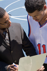 A basketball coach in a business suit sharing a play with a player on the team.   He could be also be recruiter trying to get him to sign a contract.