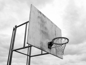 A basketball hoop found at the park in black and white.