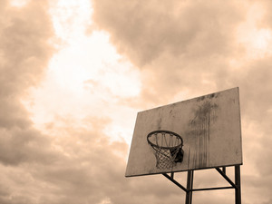 A basketball hoop found at the park in sepia tone.