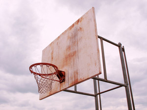 A basketball hoop found at the park that looks weathered and rusty.