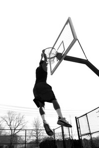 A basketball player hanging from the rim after slam dunking the ball in black and white.